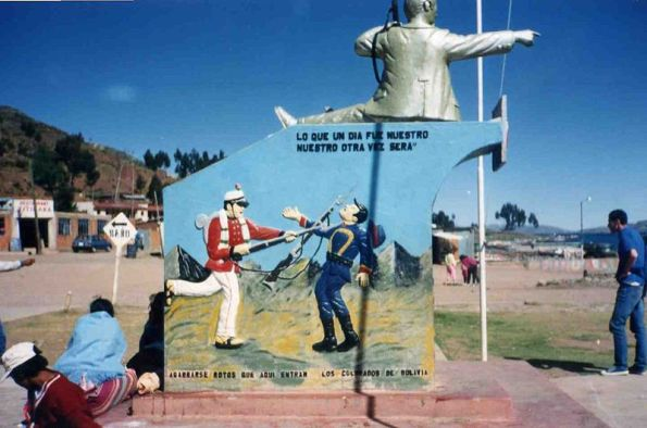 "A piece of public artwork commemorating Bolivia's losses in the War of the Pacific. The image features a statue pointing towards the Pacific Ocean and a mural of a Bolivian soldier bayoneting a Chilean soldier in the throat. The painting reads (in part), ""What once was ours, will be ours again,"" and promises Chile that Bolivia will one day return to those lands."