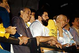 "Neves (left) with Luis Inácio Lula da Silva (center, with beard) and Ulysses Guimarães (right) during a Diretas Já (""Direct Elections Now!"") rally."